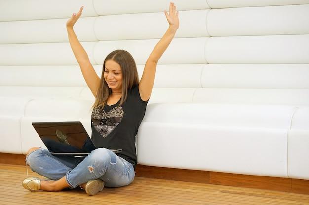 Schöne frau zu hause, die auf dem boden mit laptop sitzt