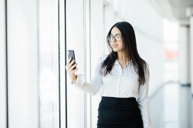 Schöne frauen benutzen das telefon am panoramafenster. geschäftskonzept
