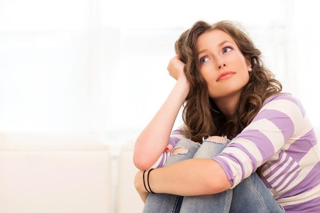 Schöne frauen denken, auf dem sofa sitzen