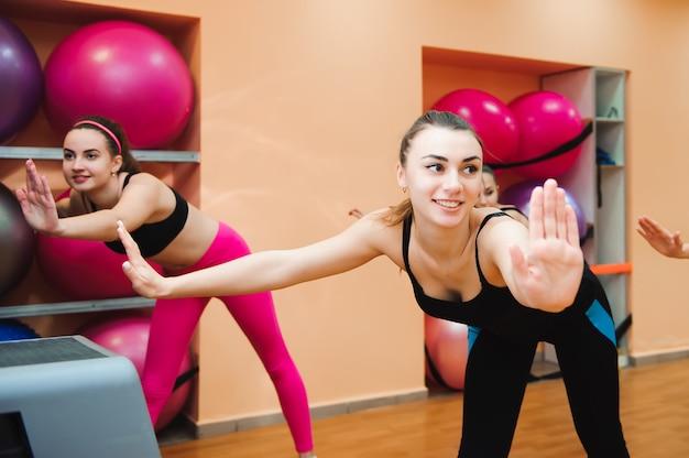 Schöne frauen, die aerobic im fitnessclub ausüben.