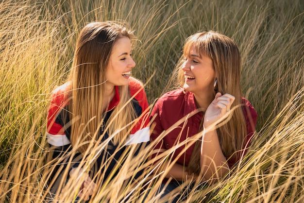 Schöne frauen, die auf gras sitzen