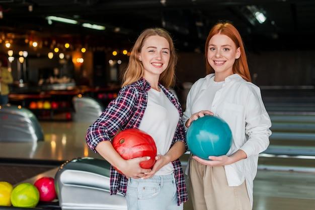 Schöne frauen, die bowlingspielkugeln anhalten