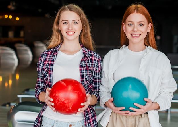 Schöne frauen, die bunte bowlingspielkugeln anhalten