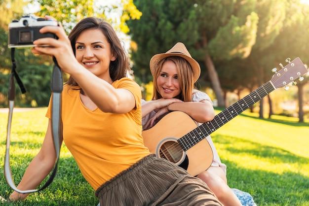 Schöne frauen, die ein selfie-porträt im park machen. freunde und sommerkonzept.