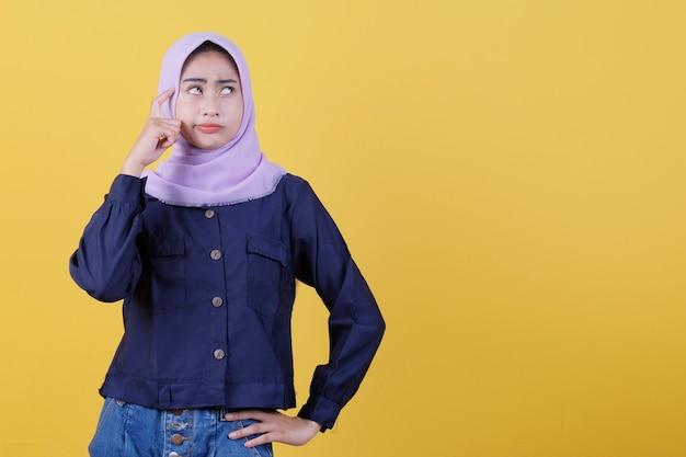 Schöne frauen, die hijabs und freizeitkleidung tragen, die ernsthaft vermutungen anstellen, richtig aussehen und im gelben hintergrund denken