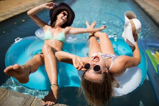 Schöne frauen, die im schwimmbad entspannen