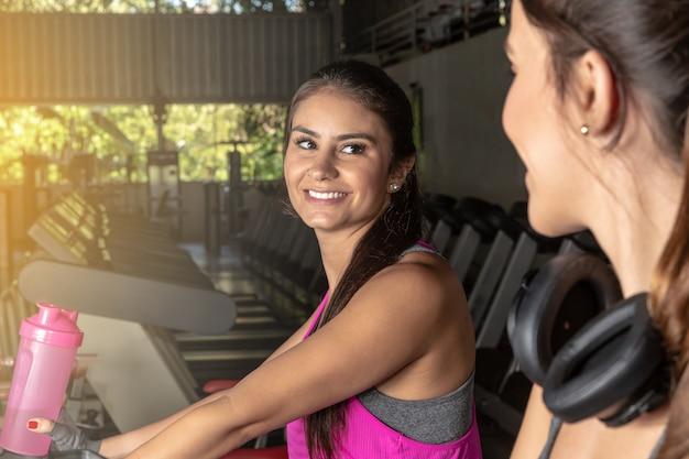 Schöne frauen, die in einer turnhalle ausbilden. schöne gruppe junge freundinnen, die auf einer tretmühle an der hellen modernen turnhalle trainieren.