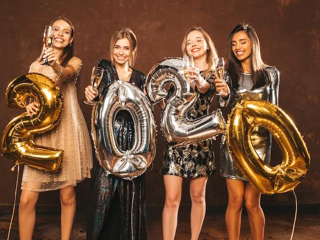 Schöne frauen, die neues jahr feiern. glückliche herrliche mädchen in den stilvollen sexy party-kleidern