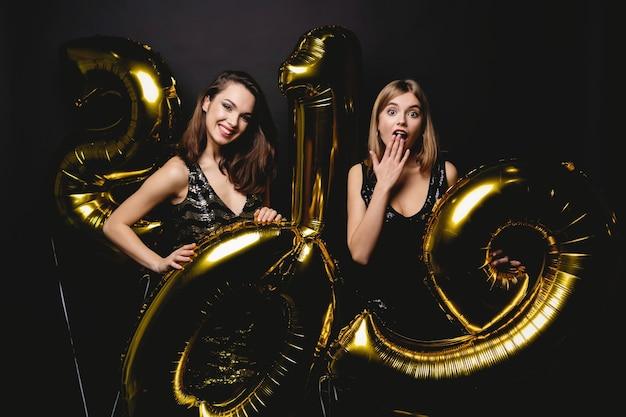 Schöne frauen, die neues jahr feiern. glückliche wunderschöne mädchen in stilvollen sexy partykleidern, die goldballons 2019 halten und spaß auf der silvesterparty haben. feiertagsfeier. hochwertiges bild