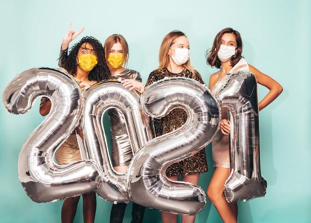 Schöne frauen, die neujahr feiern. glückliche wunderschöne frau in stilvollen sexy partykleidern, die silberne luftballons 2021 halten und spaß auf der silvesterparty haben. feiertagsfeier