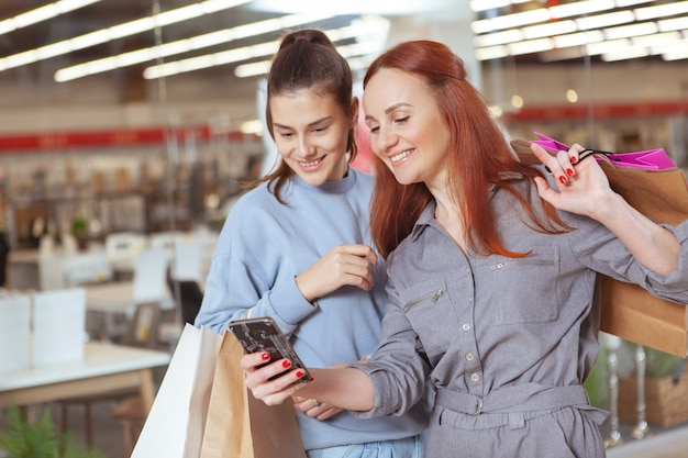 Schöne frauen, die online auf smartphone surfen, während sie mit einkaufstüten im einkaufszentrum spazieren gehen