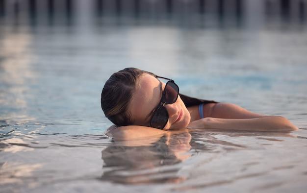 Schöne frauen, die sich am luxuriösen pool entspannen. mädchen am travel spa resort pool. sommer luxusurlaub.
