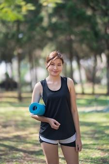 Schöne frauen, die yogamatte halten, bereiten vor, yoga im garten auszuüben