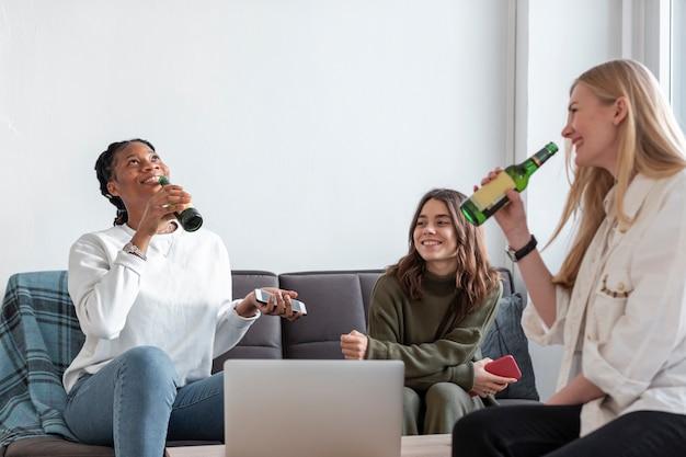 Schöne frauen, die zusammen bier trinken