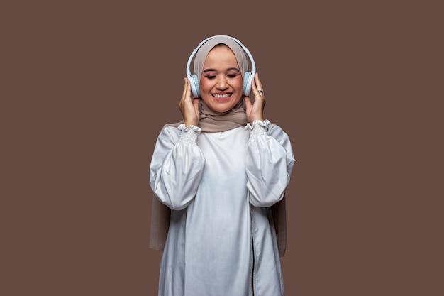 Schöne frauen im hijab mit drahtlosen kopfhörern, während sie ihre augen schließen
