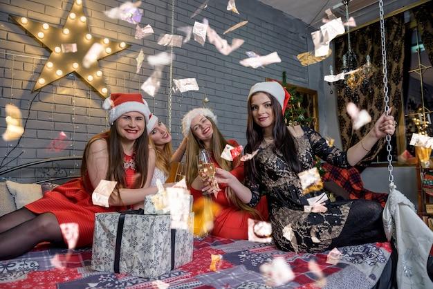 Schöne frauen in eleganten kleidern im weihnachtsstudio