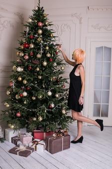 Schöne frauen in schwarzen abendkleidern nahe geschmücktem weihnachtsbaum
