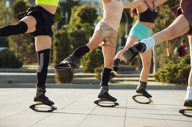 Schöne frauen in sportbekleidung, die an einem sonnigen sommertag in einem kangoo springt, springt schuhe auf der straße