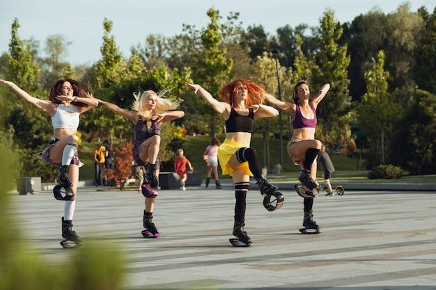 Schöne frauen in sportbekleidung, die in einem kangoo springen, springt am sonnigen sommertag schuhe auf der straße. hochspringen, aktive bewegung, action, fitness und wellness. fit weibliche models während des trainings.