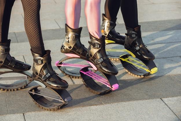 Schöne frauen in sportbekleidung mit känguru-sprungschuhen