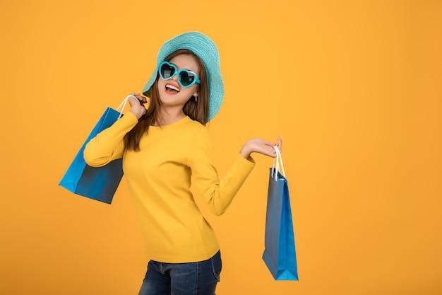 Schöne frauen kaufen im sommer mit blauen papiertüten ein