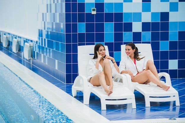 Schöne frauen liegen drinnen am chaiselongue am pool und reden Premium Fotos
