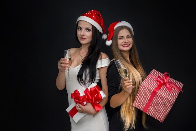 Schöne frauen mit geschenkbox und champagner