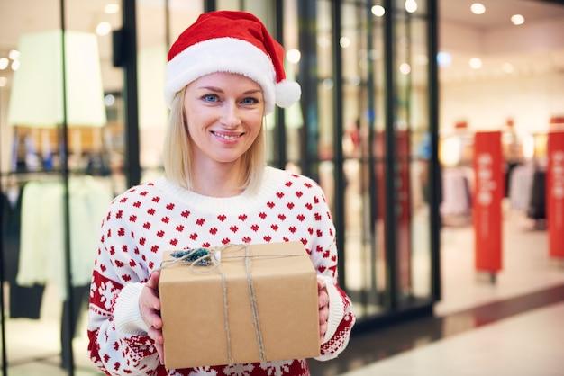 Schöne frauen mit weihnachtsmütze und weihnachtsgeschenk
