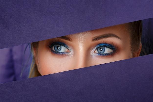 Schöne frauenaugen schauen in das papierloch, helles make-up.