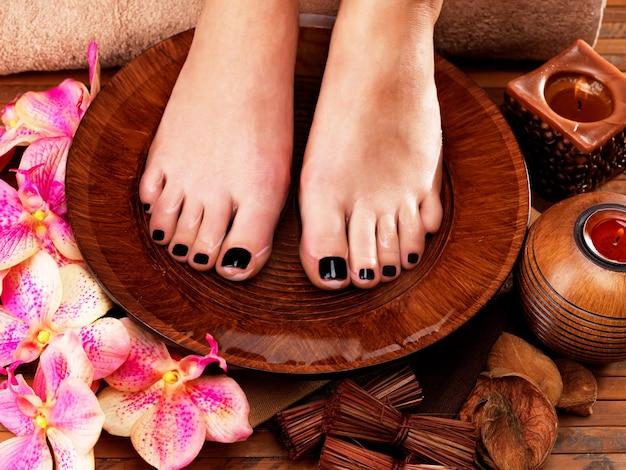 Schöne frauenbeine mit schwarzer pediküre nach spa-eingriffen - spa-behandlungskonzept