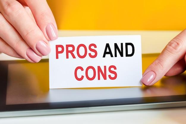 Schöne frauenhände halten ein stück weißes papier mit dem text: vor- und nachteile. kann für geschäfts-, marketing- und finanzkonzepte verwendet werden.