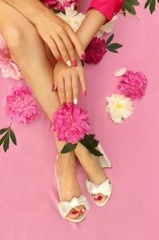 Schöne frauenhände mit maniküre und füße mit pfingstrosen in weißen sandalen und mit einer mehrfarbigen pediküre auf den nägeln.
