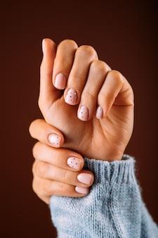 Schöne frauenhände mit rosa nägeln auf dem weißen hintergrund. nagellack in rosa farbe. maniküre, pediküre schönheitssalon konzept.