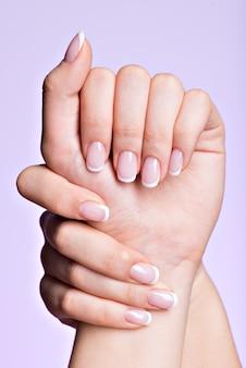 Schöne frauenhände mit schönen nägeln nach maniküresalon mit französischer maniküre