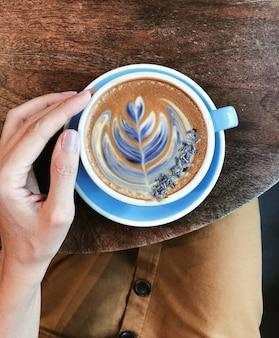 Schöne frauenhand, die einen großen blauen becher mit kaffee hält. draufsicht auf zeichnung auf kaffeeschaum. konzept eines gemütlichen und schönen frühstücks