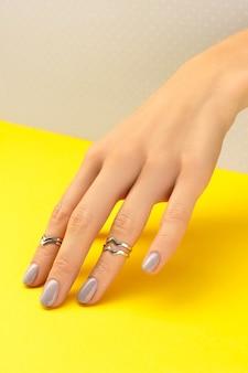 Schöne frauenhand mit glänzendem nageldesign auf grau und gelb