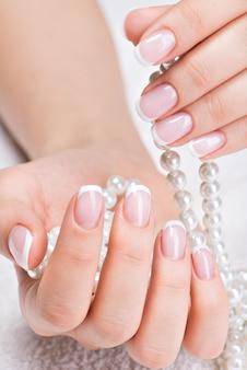 Schöne frauennägel mit schöner französischer maniküre und weißen perlen
