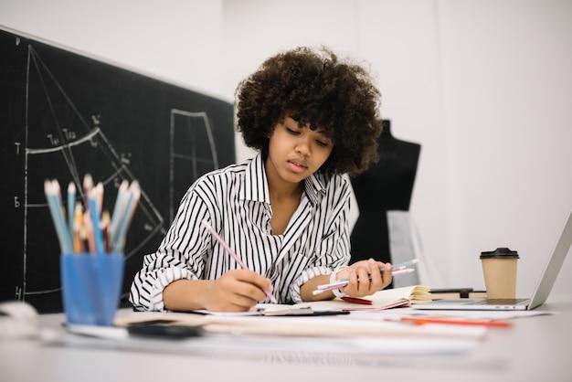 Schöne freiberuflerin der afroamerikanerin, die am arbeitsplatz skizziert oder zeichnet