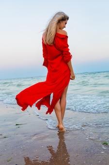 Schöne freie frau im roten kleid im wind am meeresstrand zu fuß