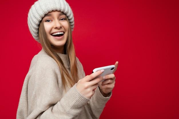 Schöne freudige glückliche junge blonde frau, die lässigen beigen pullover und beigen hut trägt