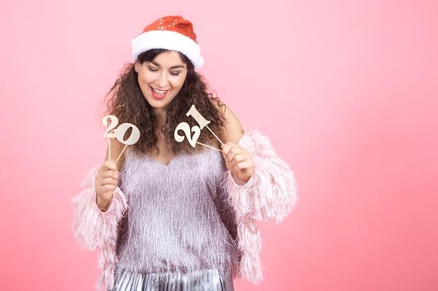 Schöne freudige junge brünette frau mit lockigem haar in einer weihnachtsmütze auf einem rosa hintergrund, der eine hölzerne zahl für das neujahrskonzept hält