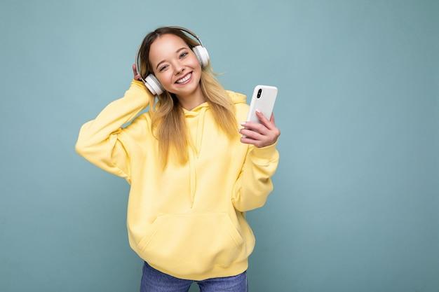 Schöne freudige lächelnde junge weibliche person, die stilvolles lässiges outfit isoliert trägt