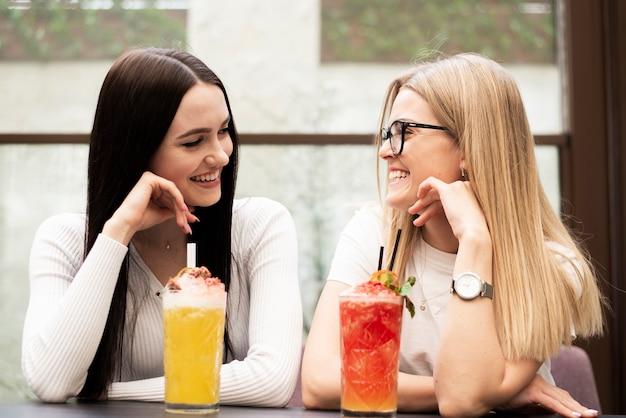 Schöne freunde der vorderansicht, die ein cocktail haben