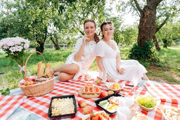 Schöne freundinnen draußen auf einem picknick mitten im park