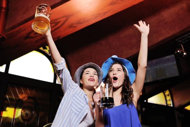 Schöne freundinnen in den bayerischen hüten einer bar, die ein bier aufpasst fußball auf einem fernsehmonitor während der feier des oktoberfestes hält