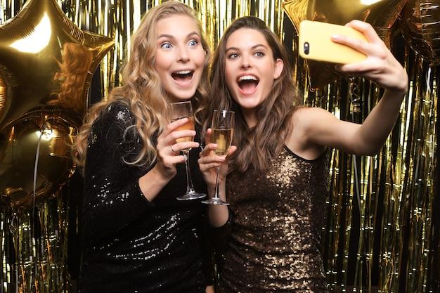 Schöne freundinnen in hochstimmung machen selfie auf der party auf goldenem hintergrund.