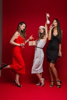 Schöne freundinnen in kleidern mit einem geschenk freuen sich zusammen, auf weiß