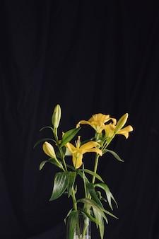 Schöne frische blumen mit grünen blättern im vase