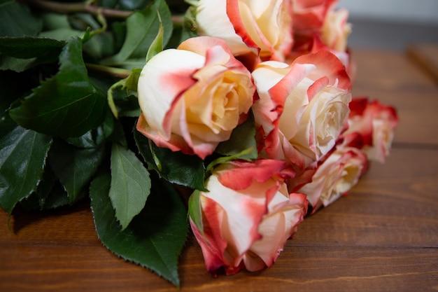 Schöne frische große rote und beige rosen liegen auf einem hölzernen hintergrund