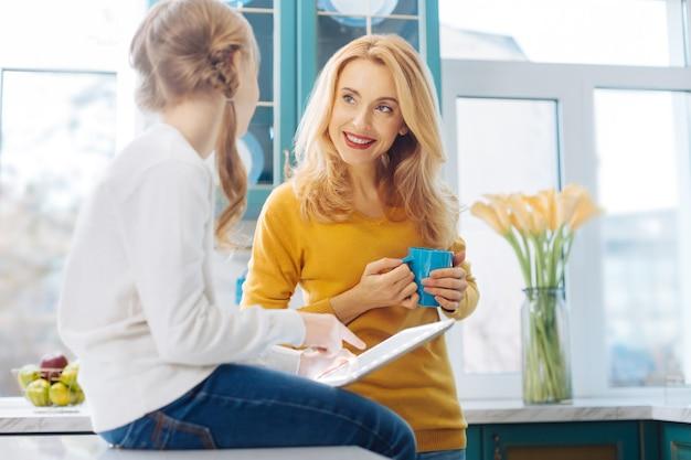 Schöne fröhliche blonde schlanke mutter, die lächelt und eine tasse tee und ihre tochter mit einer tablette hält, während sie auf dem tisch sitzt